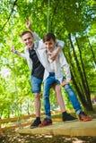 Ragazzi sorridenti divertendosi al campo da giuoco Bambini che giocano all'aperto di estate Adolescenti che guidano su un'oscilla Immagine Stock Libera da Diritti