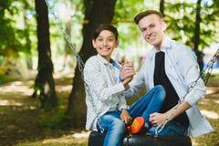 Ragazzi sorridenti divertendosi al campo da giuoco Bambini che giocano all'aperto di estate Adolescenti che guidano su un'oscilla Fotografia Stock