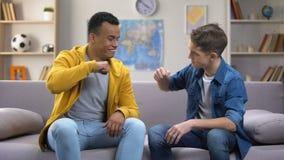 Ragazzi teenager afroamericani e caucasici allegri che urtano i pugni, riunione degli amici video d archivio