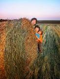 3 ragazzi in un mucchio di fieno nel campo Fotografie Stock Libere da Diritti