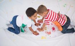 Ragazzini svegli che dipingono sul pavimento in aula Fotografia Stock