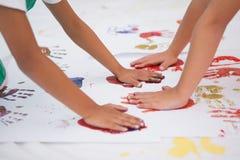 Ragazzini svegli che dipingono sul pavimento in aula Immagine Stock