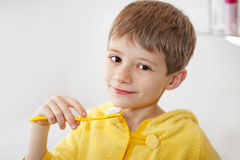 Ragazzino in accappatoio che lava i suoi denti dopo avere uguagliato bagno Fotografia Stock