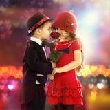 Ragazzino adorabile che dà una rosa alla ragazza Immagine Stock Libera da Diritti