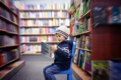 Ragazzino adorabile, sedentesi in un deposito di libro fotografie stock