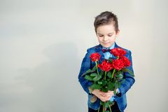 Ragazzino adorabile in vestito con il mazzo delle rose rosse su un fondo leggero fotografie stock libere da diritti