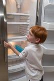 Ragazzino affamato che esamina frigorifero vuoto Immagine Stock
