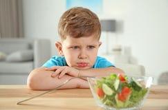 Ragazzino affilato con la ciotola di insalata di verdure alla tavola immagine stock