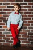 Ragazzino alla moda sveglio che resta vicino al muro di mattoni in pantaloni rossi e farfallino rosso Bambini, ragazzo fotografie stock