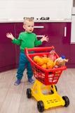 Ragazzino allegro con il carrello Bambino in carrello di compera di plastica di trasporto del bambino di abbigliamento casual Acq fotografia stock libera da diritti