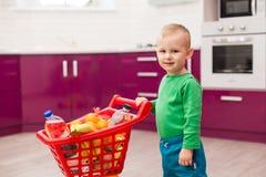Ragazzino allegro con il carrello Bambino in carrello di compera di plastica di trasporto del bambino di abbigliamento casual Acq immagine stock
