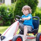 Ragazzino attivo divertendosi e conducendo la macchina da corsa del giocattolo immagini stock