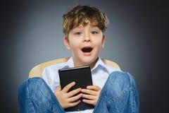Ragazzino bello con sorridere del libro elettronico isolato su fondo grigio Fotografia Stock