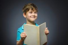 Ragazzino bello con sorridere del libro isolato su fondo grigio Immagine Stock