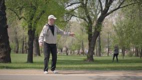 Ragazzino in camicia a quadretti che rollerblading nel parco, suo nonno che prende lui ed abbracciare Svago attivo stock footage
