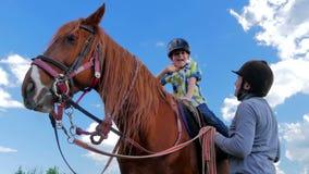 Ragazzino in casco che si siede sul cavallo e sulla mano d'ondeggiamento stock footage