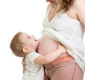 Ragazzino che abbraccia la pancia della madre incinta e che guarda su Immagine Stock