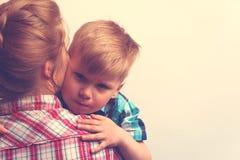 Ragazzino che abbraccia sua madre dopo il dispiacere Fotografia Stock