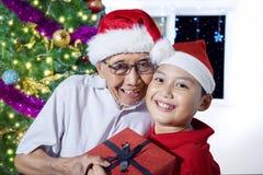 Ragazzino che abbraccia suo nonno al tempo di Natale Fotografie Stock Libere da Diritti