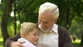 Ragazzino che cammina al nonno che si siede sul banco e che lo abbraccia con amore archivi video