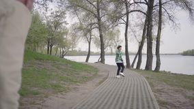 Ragazzino che corre da suo nonno nel parco, vuole andare al fiume L'uomo anziano non pu? seguire il ragazzo, lui stock footage