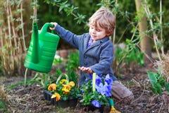 Ragazzino che fa il giardinaggio e che pianta i fiori in giardino Fotografie Stock