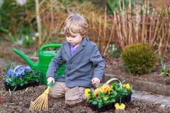Ragazzino che fa il giardinaggio e che pianta i fiori in giardino Immagine Stock