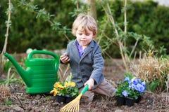 Ragazzino che fa il giardinaggio e che pianta i fiori in giardino Fotografia Stock Libera da Diritti