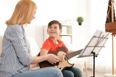 Ragazzino che gioca chitarra con il suo insegnante Apprendimento delle note fotografia stock
