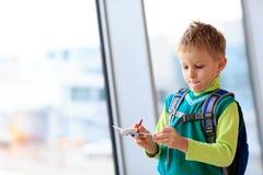 Ragazzino che gioca con l'aereo del giocattolo nell'aeroporto Immagini Stock