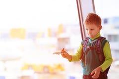 Ragazzino che gioca con l'aereo del giocattolo nell'aeroporto Fotografia Stock Libera da Diritti