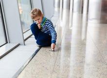 Ragazzino che gioca con l'aereo del giocattolo nell'aeroporto Immagini Stock Libere da Diritti