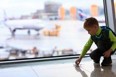 Ragazzino che gioca con l'aereo del giocattolo nell'aeroporto Fotografie Stock Libere da Diritti