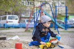 Ragazzino che gioca con l'escavatore dei bambini nella sabbiera Fotografie Stock