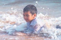 Ragazzino che gioca con l'onda e la sabbia sulla spiaggia di Pattaya fotografie stock libere da diritti