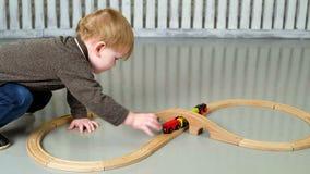 Ragazzino che gioca con la ferrovia di legno archivi video