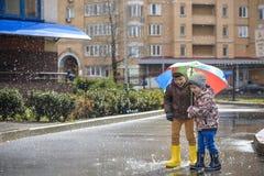 Ragazzino che gioca nel parco piovoso di estate Il bambino con l'ombrello variopinto dell'arcobaleno, impermeabilizza il cappotto immagine stock