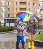 Ragazzino che gioca nel parco piovoso di estate Il bambino con l'ombrello variopinto dell'arcobaleno, impermeabilizza il cappotto fotografie stock libere da diritti