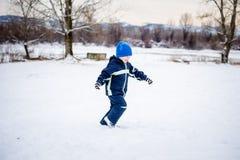 Ragazzino che gioca nella neve fotografia stock libera da diritti