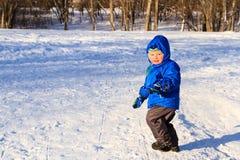 Ragazzino che gioca nella neve di inverno Immagini Stock