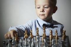 Ragazzino che gioca scacchi Bambino astuto Piccolo bambino del genio Gam intelligente Fotografie Stock Libere da Diritti