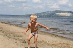 Ragazzino che gioca sulla spiaggia vicino al fiume Fotografia Stock Libera da Diritti