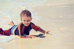 Ragazzino che gode del mare sulla vacanza della spiaggia Immagine Stock