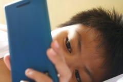 Ragazzino che guarda su uno smartphone Fotografie Stock