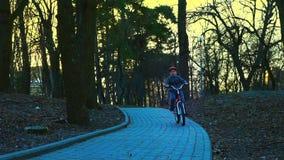 Ragazzino che guida la bicicletta nel parco, parco del tramonto, movimento lento video d archivio