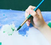 Ragazzino che impara concetto di arte del disegno della pittura La mano del bambino tiene una spazzola e le pitture su Libro Bian Immagine Stock Libera da Diritti