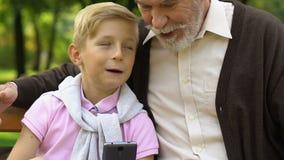 Ragazzino che insegna a suo nonno che per mezzo dello Smart Phone per fare una chiamata, tecnologia video d archivio