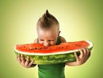 Ragazzino che mangia una grande fetta di anguria Fotografie Stock