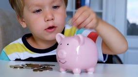 Ragazzino che mette le monete in un porcellino salvadanaio stock footage