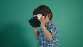 Ragazzino che per mezzo del dispositivo di realtà virtuale sopra la parete verde archivi video